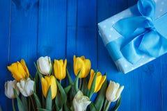 Τα λουλούδια τουλιπών άνοιξη, το κιβώτιο δώρων και η κάρτα εγγράφου στον μπλε ξύλινο πίνακα άνωθεν στο επίπεδο βάζουν το ύφος Στοκ φωτογραφία με δικαίωμα ελεύθερης χρήσης