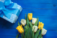 Τα λουλούδια τουλιπών άνοιξη, το κιβώτιο δώρων και η κάρτα εγγράφου στον μπλε ξύλινο πίνακα άνωθεν στο επίπεδο βάζουν το ύφος Στοκ εικόνα με δικαίωμα ελεύθερης χρήσης