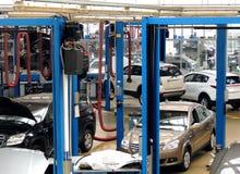 Τα οχήματα στο εργαστήριο επισκευής με το αυτοκίνητο ανυψώνουν τη φωτογραφία αποθεμάτων Στοκ φωτογραφία με δικαίωμα ελεύθερης χρήσης