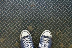 Τα πάνινα παπούτσια, εξερευνούν τον κόσμο Αθλητικά πάνινα παπούτσια από μια εναέρια άποψη σχετικά με τη σύσταση μετάλλων Στοκ εικόνα με δικαίωμα ελεύθερης χρήσης