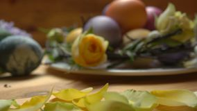 Τα πέταλα ενός κίτρινου αυξήθηκαν πτώση σε έναν πίνακα με τα αυγά Πάσχας απόθεμα βίντεο