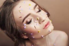 Τα πέταλα λουλουδιών στο κορίτσι προσώπου, καλλυντικά γυναικών για να ενυδατώσουν το δέρμα προσώπου, μειώνουν τις ρυτίδες, καθαρό στοκ εικόνες