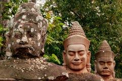 Τα πέτρινα επικεφαλής αγάλματα σε Angkor Wat, Siem συγκεντρώνουν, Καμπότζη, Indochina, Ασία - αντιμετωπίστε επάνω στο χρώμα στοκ εικόνες