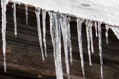 Τα παγάκια κρεμούν από τη στέγη του σπιτιού ο μπλε παγετός σκοτεινής μέρας κλάδων βρίσκεται χειμώνας δέντρων χιονιού ουρανού Στοκ Εικόνες