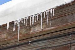 Τα παγάκια κρεμούν από τη στέγη του σπιτιού ο μπλε παγετός σκοτεινής μέρας κλάδων βρίσκεται χειμώνας δέντρων χιονιού ουρανού Στοκ Φωτογραφία