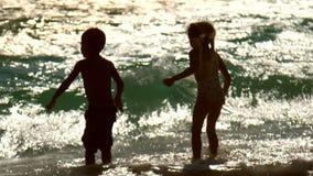 Τα παιδιά έχουν τη διασκέδαση στα κύματα ηλιοβασιλέματος ευτυχείς διακοπές Τα παιδιά απολαμβάνουν το νερό φιλμ μικρού μήκους