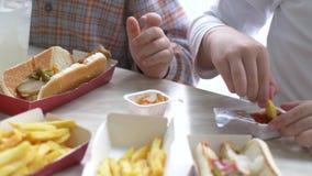 Τα παιδιά έχουν το μεσημεριανό γεύμα στον καφέ γρήγορου φαγητού Τα αγόρια πίνουν τη λεμονάδα και τρώνε τα χάμπουργκερ στο υπόβαθρ απόθεμα βίντεο