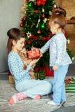 Τα παιδιά, αδελφές, ανοίγουν τα δώρα Η έννοια των Χριστουγέννων και του νέου YE Στοκ φωτογραφία με δικαίωμα ελεύθερης χρήσης