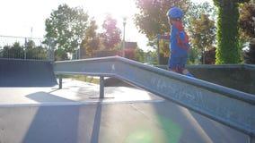 Τα παιδιά αμφισβητούν, το μικρό παιδί στα σαλάχια κυλίνδρων ξοδεύει τον ελεύθερο χρόνο σε Sportsground φιλμ μικρού μήκους