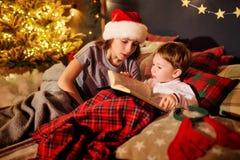 Τα παιδιά διαβάζουν ένα βιβλίο στο δωμάτιο Χριστουγέννων Στοκ Φωτογραφίες