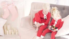 Τα παιδιά κάθονται στο σπίτι στον καναπέ απόθεμα βίντεο