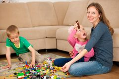 Τα παιδιά και η μητέρα τους παίζουν με τους φραγμούς στο έδαφος Στοκ φωτογραφία με δικαίωμα ελεύθερης χρήσης