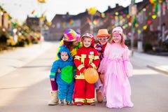 Τα παιδιά και οι γονείς στο τέχνασμα αποκριών ή μεταχειρίζονται Στοκ εικόνα με δικαίωμα ελεύθερης χρήσης