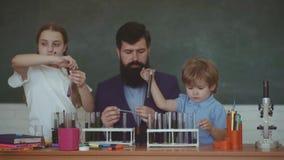 Τα παιδιά και ο δάσκαλος μαθαίνουν στην κατηγορία στο υπόβαθρο του πίνακα o Ευτυχές σχέδιο μαθητών χαμόγελου φιλμ μικρού μήκους
