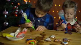 Τα παιδιά καλύπτουν με κέικ ενός τα ζωηρόχρωμα λούστρου, δίπλα στο χριστουγεννιάτικο δέντρο απόθεμα βίντεο