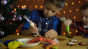 Τα παιδιά καλύπτουν με κέικ ενός τα ζωηρόχρωμα λούστρου, δίπλα στο χριστουγεννιάτικο δέντρο φιλμ μικρού μήκους