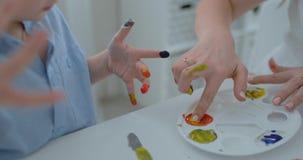 Τα παιδιά κινηματογραφήσεων σε πρώτο πλάνο επισύρουν την προσοχή τα δάχτυλά τους σε χαρτί χρησιμοποιώντας τα χρώματα απόθεμα βίντεο