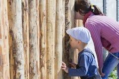 Τα παιδιά κοιτάζουν μέσω της τρύπας στο φράκτη στοκ εικόνες