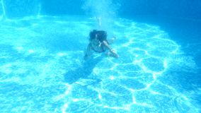 Τα παιδιά κολυμπούν κάτω από το νερό κορίτσι με τις μακρυμάλλεις καταδύσεις στο νερό 4K κίνηση αργή απόθεμα βίντεο