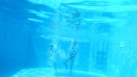 Τα παιδιά κολυμπούν κάτω από το νερό 4K κίνηση αργή αγόρι και κορίτσι που βουτούν στο νερό από κοινού φιλμ μικρού μήκους