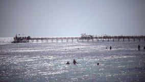 Τα παιδιά λούζουν στον ωκεανό και στην αποβάθρα οι άνθρωποι αναπνέουν τη θαλάσσια αύρα απόθεμα βίντεο