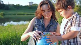 Τα παιδιά μαθαίνουν τον κόσμο, ο περίεργος έφηβος αγοριών και κοριτσιών εξετάζει τη σφαίρα στη συνεδρίαση φύσης στη χλόη κοντά στ απόθεμα βίντεο
