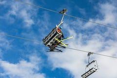 Τα παιδιά με τα σκι κάθονται σε ένα τελεφερίκ Οι σκιέρ με τα ζωηρόχρωμα σκι οδηγούν σε ένα τελεφερίκ στο λόφο στους δολομίτες Alp Στοκ Εικόνα