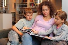 Τα παιδιά με τη μητέρα κάθονται στον καναπέ και διαβάζουν το βιβλίο στοκ εικόνα με δικαίωμα ελεύθερης χρήσης
