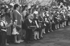 Τα παιδιά με τις ανθοδέσμες των λουλουδιών εγγράφτηκαν στην πρώτη τάξη στο σχολείο με τους δασκάλους και τους μαθητές σε έναν σοβ Στοκ εικόνες με δικαίωμα ελεύθερης χρήσης