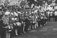 Τα παιδιά με τις ανθοδέσμες των λουλουδιών εγγράφτηκαν στη πρώτη θέση με τους δασκάλους στη σχολική ` s σοβαρή γραμμή στην ημέρα  Στοκ Φωτογραφίες