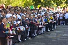 Τα παιδιά με τις ανθοδέσμες των λουλουδιών εγγράφτηκαν στη πρώτη θέση με τους δασκάλους και τους σπουδαστές γυμνασίου στη σχολική Στοκ Φωτογραφίες