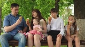 Τα παιδιά με τους γονείς κάθονται στο πάρκο στον πάγκο τρώγοντας το παγωτό και το γέλιο οικογένεια ευτυχής απόθεμα βίντεο