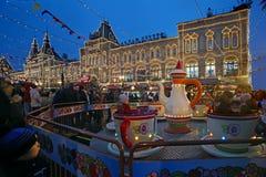 Τα παιδιά οδηγούν ένα ιπποδρόμιο στην κόκκινη πλατεία που διακοσμείται στο νέο έτος ` s Στοκ Εικόνες