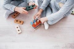Τα παιδιά παίζουν με έναν σχεδιαστή παιχνιδιών στο πάτωμα του δωματίου παιδιών ` s ζωηρόχρωμα απομονωμένα κατσίκια ομάδων δεδομέν στοκ φωτογραφία με δικαίωμα ελεύθερης χρήσης