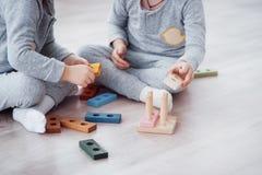 Τα παιδιά παίζουν με έναν σχεδιαστή παιχνιδιών στο πάτωμα του δωματίου παιδιών ` s ζωηρόχρωμα απομονωμένα κατσίκια ομάδων δεδομέν στοκ εικόνες