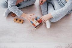 Τα παιδιά παίζουν με έναν σχεδιαστή παιχνιδιών στο πάτωμα του δωματίου παιδιών ` s ζωηρόχρωμα απομονωμένα κατσίκια ομάδων δεδομέν στοκ εικόνα με δικαίωμα ελεύθερης χρήσης