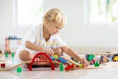 Τα παιδιά παίζουν τον ξύλινο σιδηρόδρομο Παιδί με το τραίνο παιχνιδιών στοκ φωτογραφία με δικαίωμα ελεύθερης χρήσης