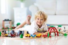 Τα παιδιά παίζουν τον ξύλινο σιδηρόδρομο Παιδί με το τραίνο παιχνιδιών στοκ φωτογραφία