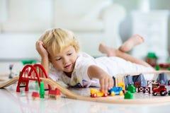 Τα παιδιά παίζουν τον ξύλινο σιδηρόδρομο Παιδί με το τραίνο παιχνιδιών στοκ φωτογραφίες
