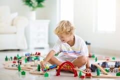 Τα παιδιά παίζουν τον ξύλινο σιδηρόδρομο Παιδί με το τραίνο παιχνιδιών στοκ εικόνες