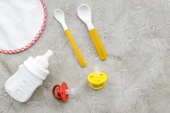 Τα παιδιά που ταΐζουν με τον τύπο μητρικού γάλακτος ή νηπίων κονιοποίησαν το γάλα και τα παιχνίδια μωρών στο γκρίζο πρότυπο άποψη Στοκ Εικόνα