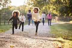 Τα παιδιά που τρέχουν μπροστά ως πολυ οικογένεια παραγωγής απολαμβάνουν τον περίπατο φθινοπώρου στην επαρχία από κοινού στοκ φωτογραφίες