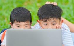 Τα παιδιά που χρησιμοποιούν το lap-top, έννοια θερινών σχολείων, ασιατικά παιδιά παίζουν το φορητό προσωπικό υπολογιστή στο πάρκο στοκ εικόνες