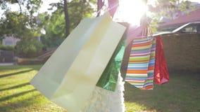 Τα παιδιά που ψωνίζουν, μικρός αγοραστής κοριτσιών χαίρονται για τις νέες αγορές στις συσκευασίες και αυξάνουν τα χέρια επάνω στο φιλμ μικρού μήκους