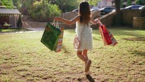 Τα παιδιά που ψωνίζουν, μικρό κορίτσι πηδούν με πολλές συσκευασίες στα χέρια μετά από τις αγορές υπαίθρια απόθεμα βίντεο