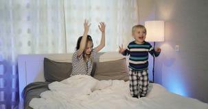 Τα παιδιά προσέχουν τη TV και το χορό στο κρεβάτι απόθεμα βίντεο