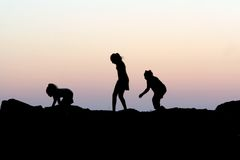 τα παιδιά σκιαγραφούν το ηλιοβασίλεμα Στοκ Εικόνες