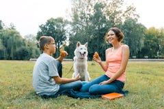 Τα παιδιά στηρίζονται στο πάρκο στον πράσινο χορτοτάπητα με ένα άσπρο σκυλί γεροδεμένο, που τρώει croissants, ομιλία στοκ εικόνες