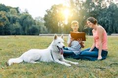 Τα παιδιά στηρίζονται στο πάρκο στον πράσινο χορτοτάπητα με ένα άσπρο σκυλί γεροδεμένο, διαβάζοντας το βιβλίο, ομιλία στοκ εικόνες