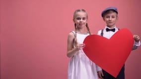 Τα παιδιά συνδέουν το κράτημα της κόκκινης διακοπής καρδιών και το χαμόγελο, ημέρα βαλεντίνων, έννοια αγάπης απόθεμα βίντεο